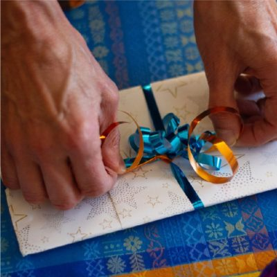 Hands tie a ribbon on a gift,