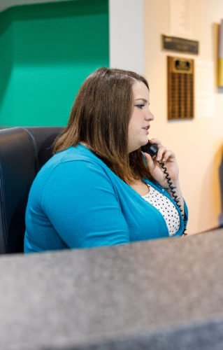Receptionist directing calls at front desk