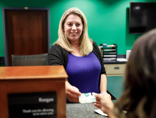 Teller giving debit card back to member